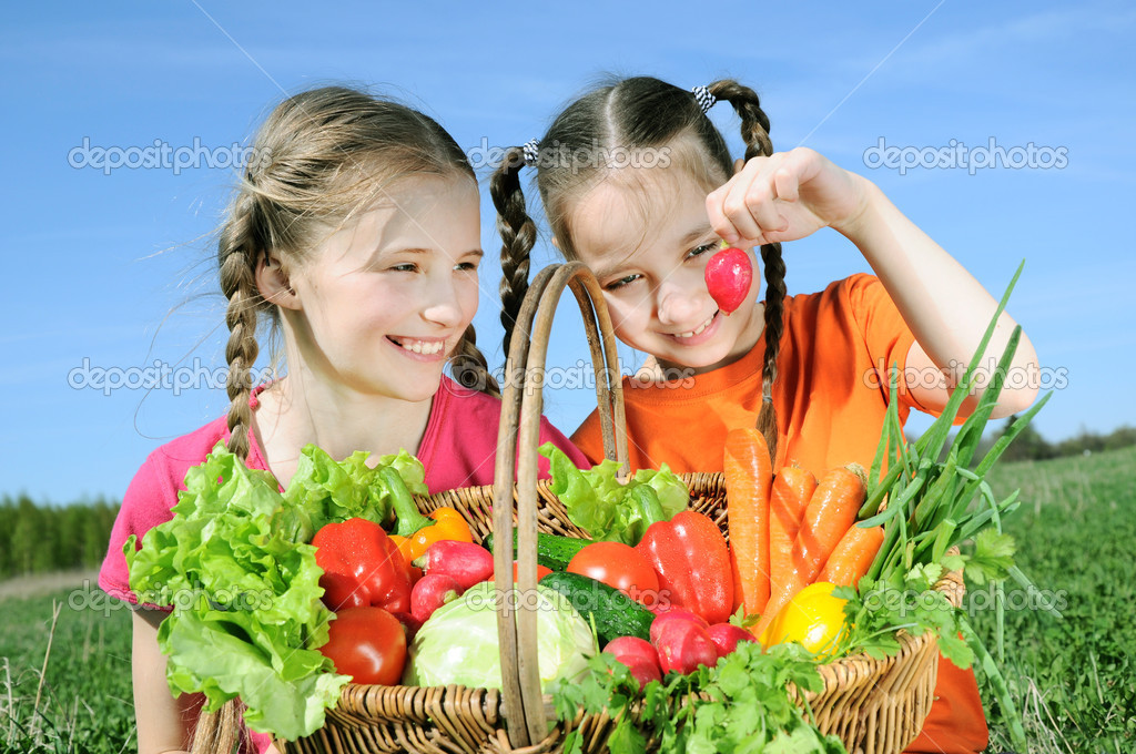 Two girls with basket of vegetables