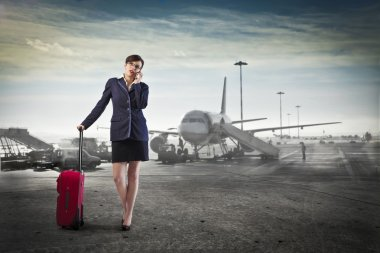 Young businesswoman at the airport holding a trolley case and talking on the mobile phone