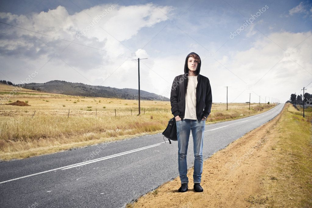 Young man standing on a country road