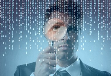 Young businessman observing a binary code on a screen through a magnifying glass