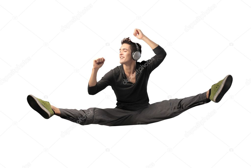 Handsome young man dancing while listening to music
