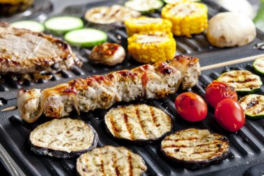 Meat skewer and vegetables on electric grill