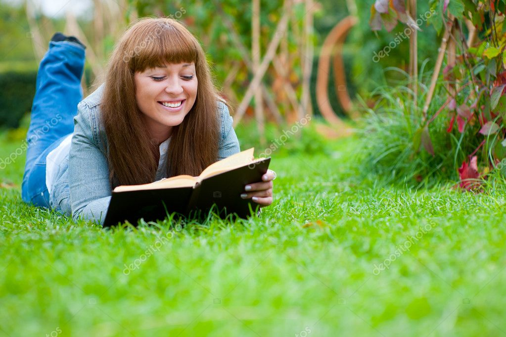 Young woman reading a book lying on the grass