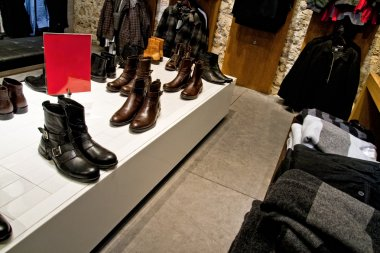 Many shoes and clothes on shop store shelves