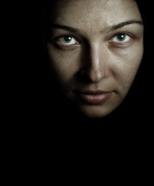 Face and eyes of spooky mystery woman in the dark