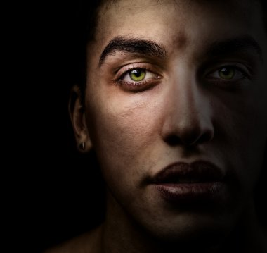 Face of beautiful man with green eyes in the shadow