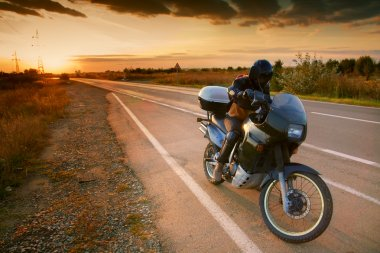 Biker and motorcycle on road at sunset