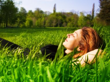 Serene woman relaxing outdoor in fresh grass