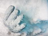 pohřben zaživa. jedna rukavice trčí z závěji s tmavě modré stíny.