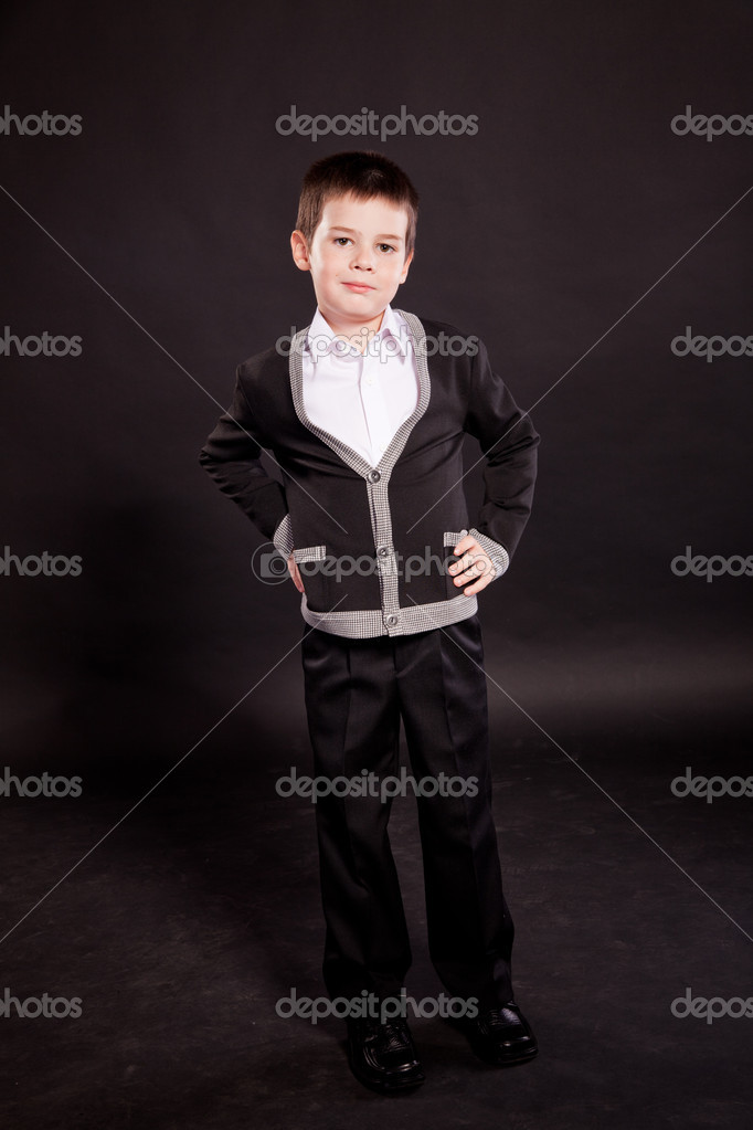 93ec69edfcd9 Young boy posing in studio in a dark suit and a red tie with an umbrella,  business dress code, on black in studio — Photo by ...