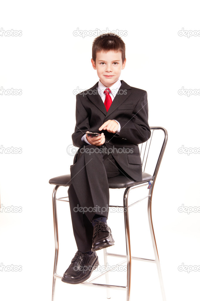 5ac187fdbd81 Young boy posing in studio in a dark suit and a red tie sitting on a chair  and talking on mobile phone, business dress code, isolated on white — Photo  by ...