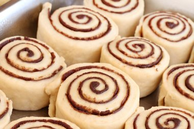 Raw cinnamon buns ready to bake with selective focus.
