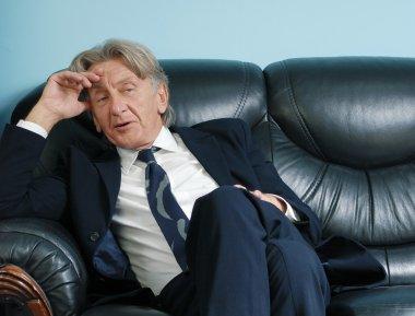 Director thinking on leather sofa. Attractive seniors studio shots series. stock vector