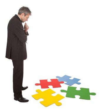Senior businessman assembling a jigsaw puzzle