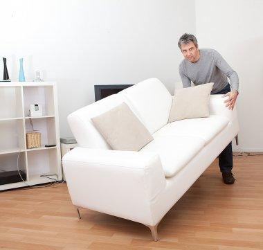 Senior man moving sofa