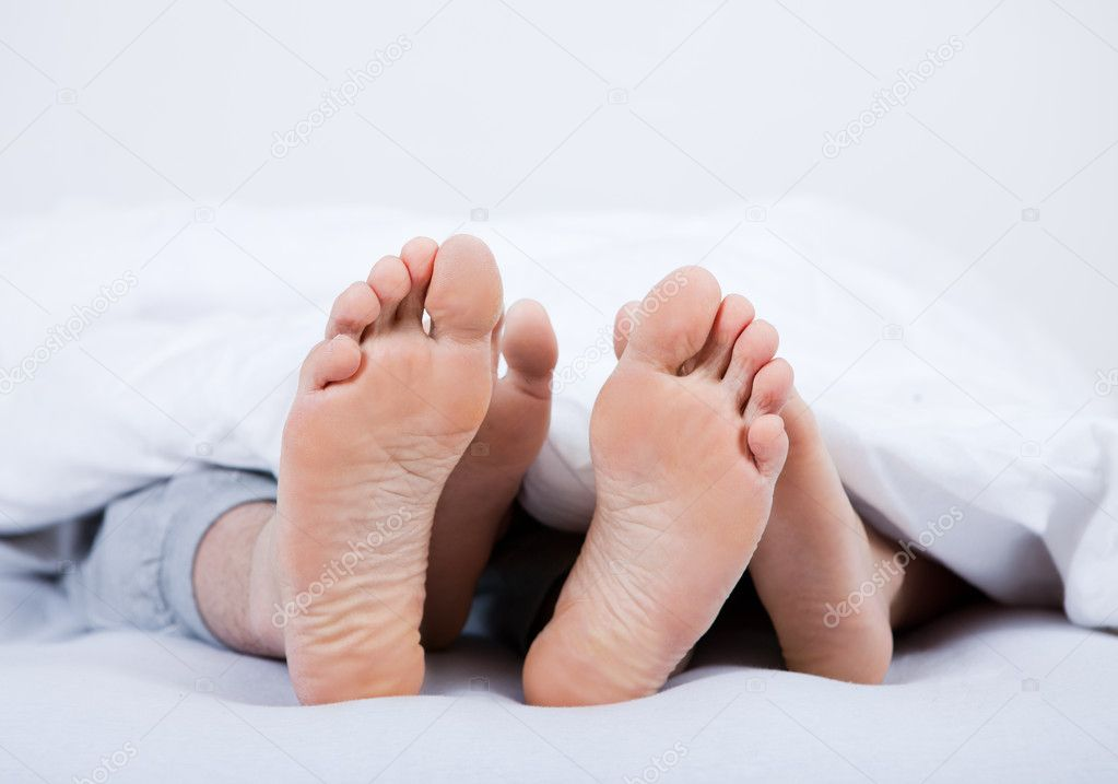 Feet of a couple under the blanket