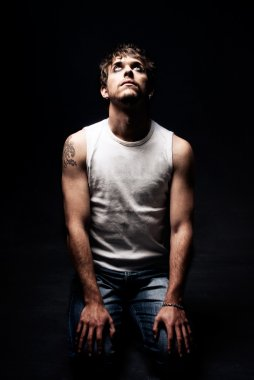 Rude man on knees looking up tattoo dark on black background