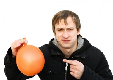 Dissatisfied young man hold a balloon which is blown off