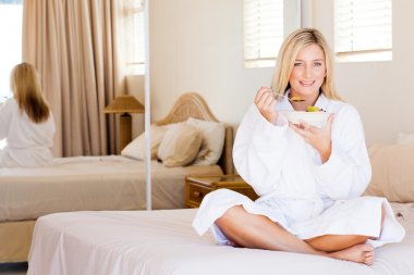 Young woman eating salad in bedroom