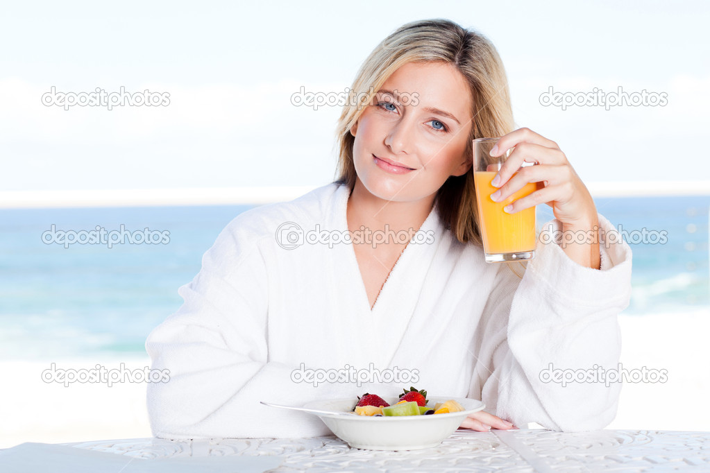 Young woman drinking orange juice at breakfast table