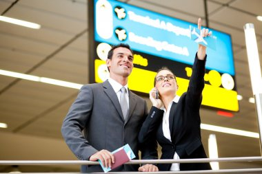Business travellers checking boarding information