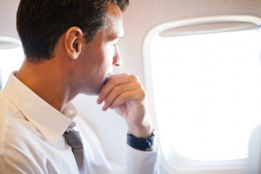 Thoughtful businessman on airplane
