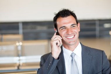 Happy businessman talking on cell phone at airport