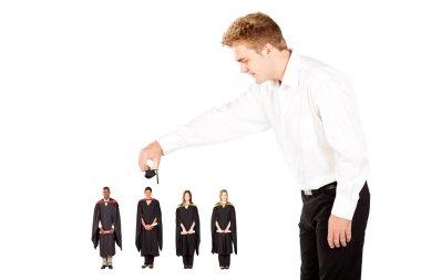 Man putting cap on university graduate
