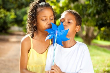 Kids blowing on a pinwheel