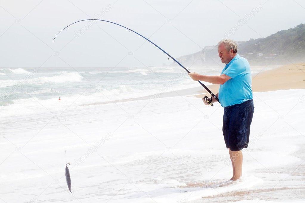 Senior man catching fish on beach