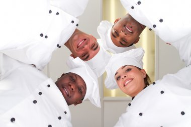 Group of professional chefs heads together form a team