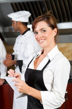Young happy waitress in restaurant kitchen