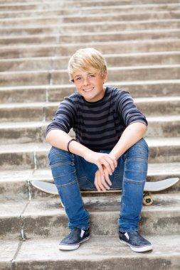 Teen boy sitting on skateboard