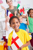 Fotografie Group of preschool kids and teacher with flags in classroom