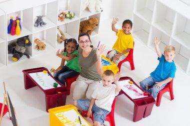 Preschool teacher and students in classroom