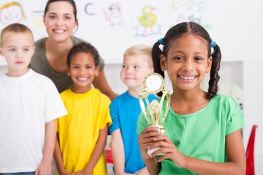 Preschool girl holding a trophy in front of classmates