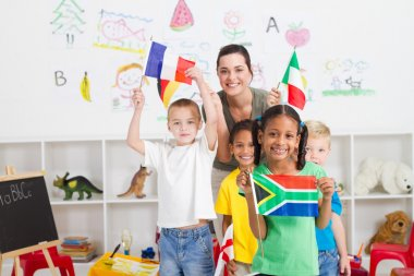 Preschool kids and teacher with flags in classroom