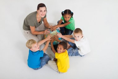 Preschool teacher and students hands on a globe