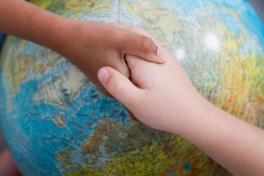 Kids handshake on globe