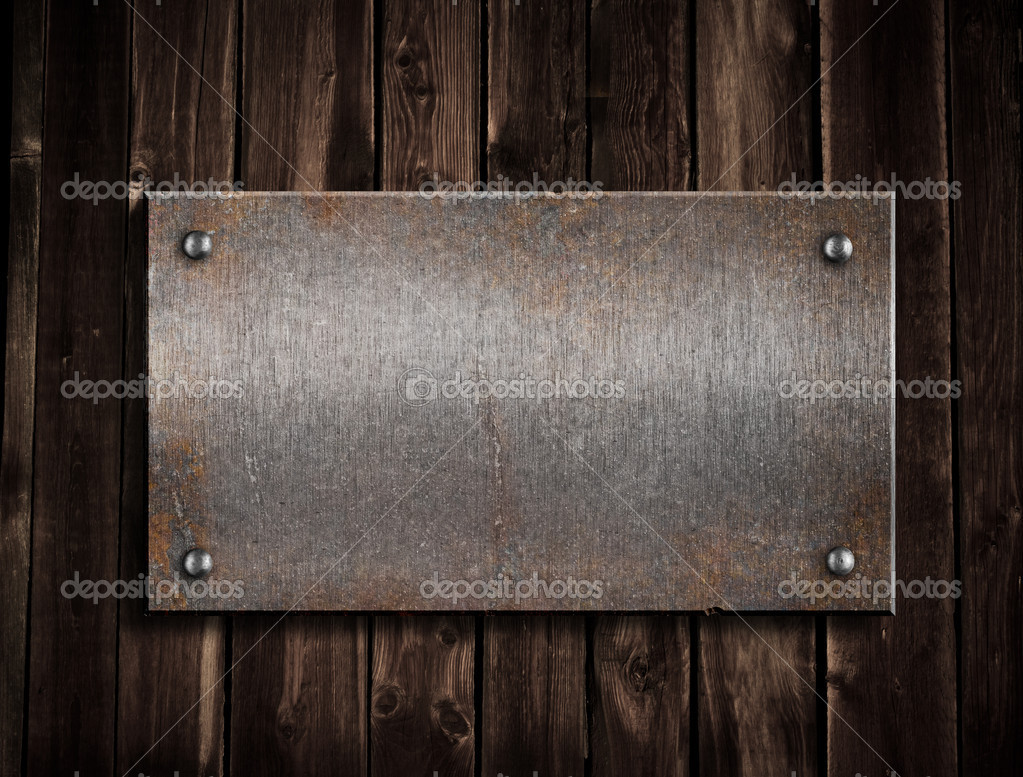 Rusty metal plate on wooden background stock photo for Plaque de metal adhesive