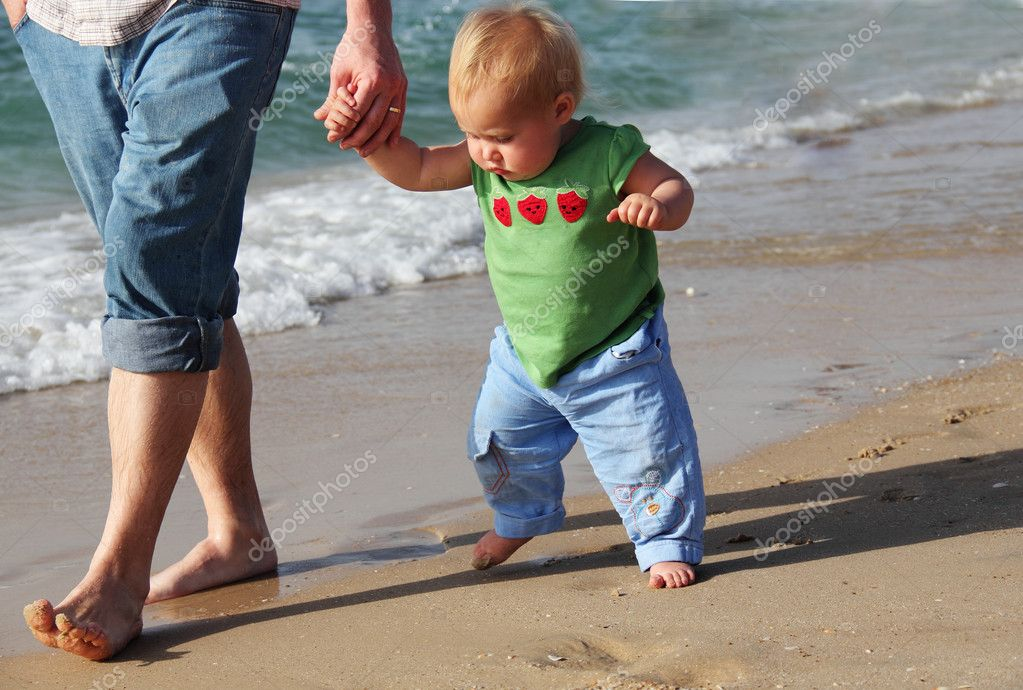 Child taking her first steps. Father and daughter of the sea.