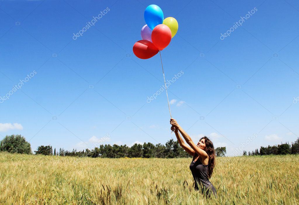 Young woman with colorful balloons. Photo in old image style.
