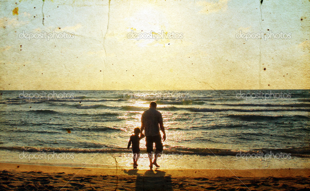 Father and son at sea watching the sunse