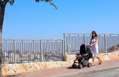 Young mother walking with a stroller on the background of a big