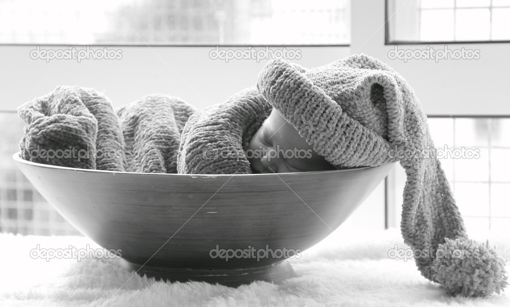 Newborn in a knitted cocoon and hat