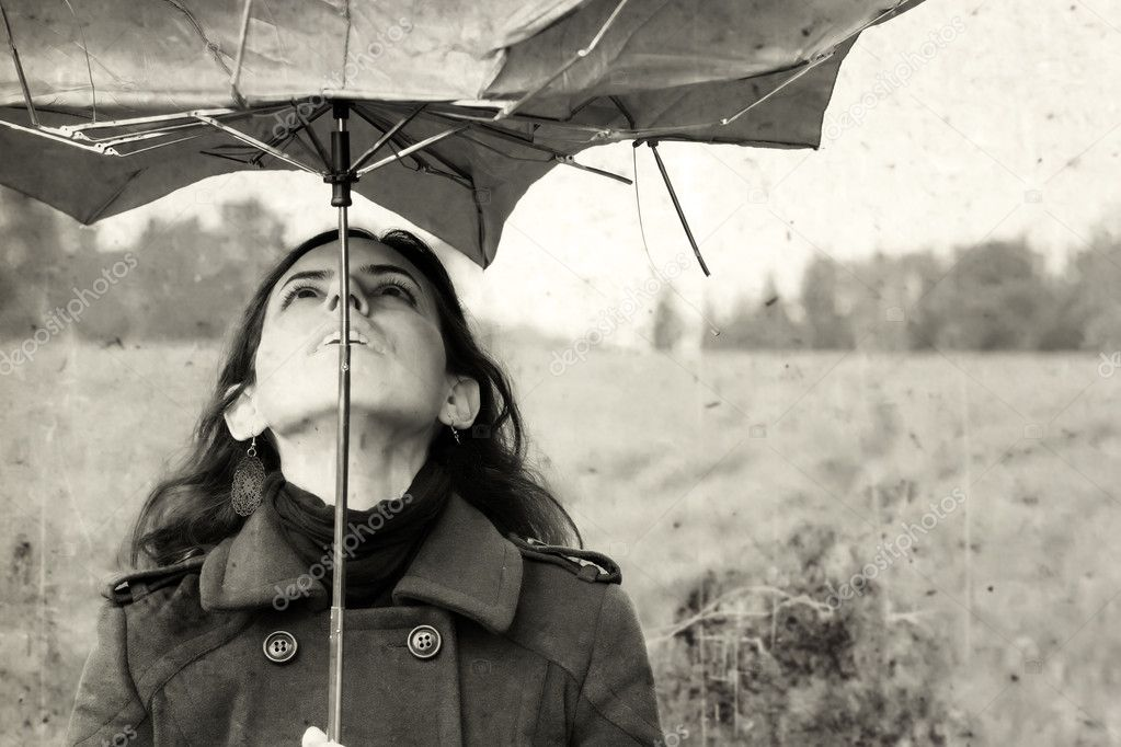 Girl with umbrella in the field. Photo in old color image style.