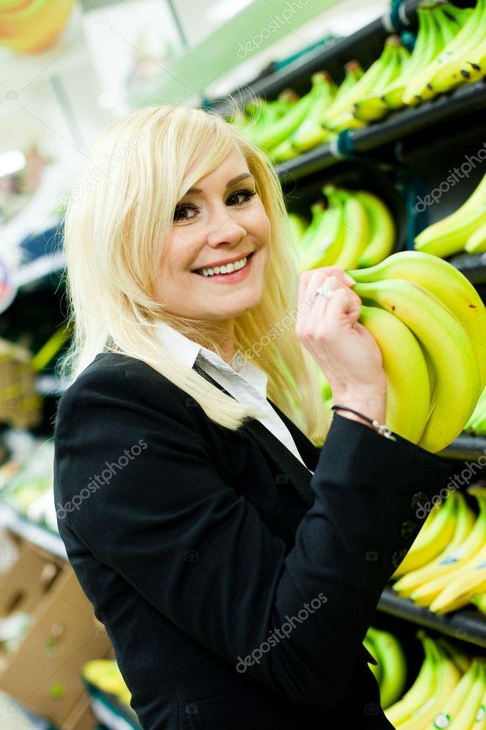 femme souriante acheter des bananes photographie nelka7812 10343291. Black Bedroom Furniture Sets. Home Design Ideas