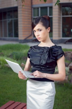 Portrait of young business woman holding netbook