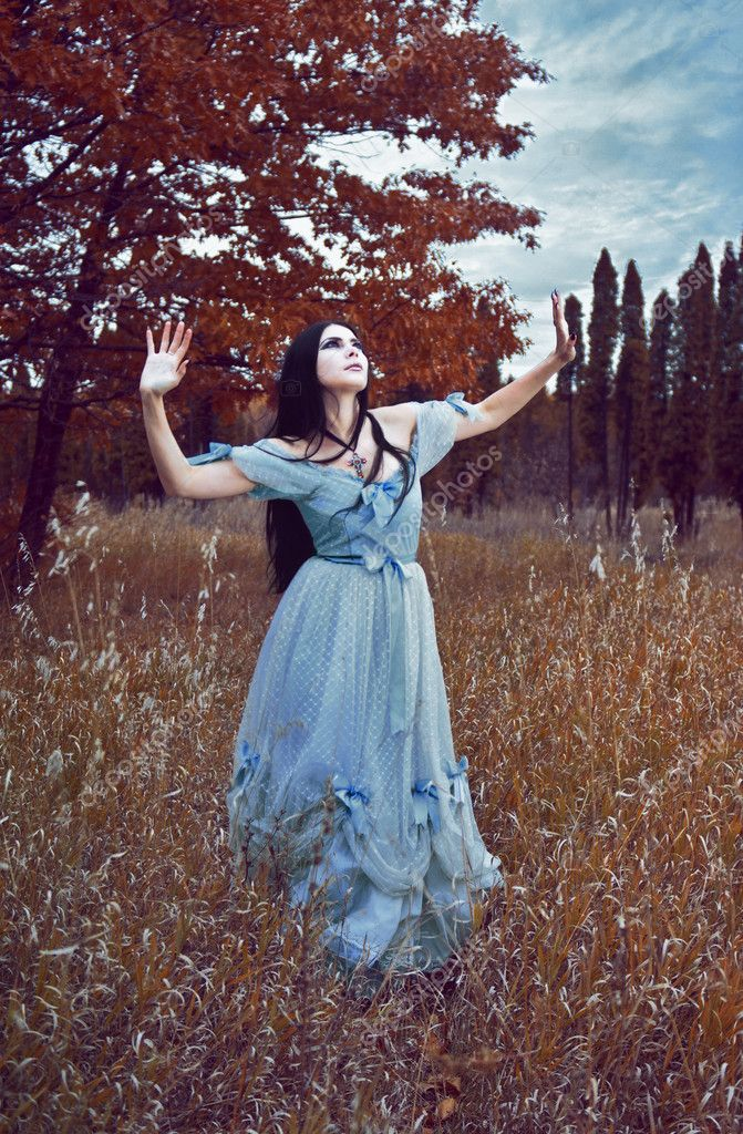 Gothic girl outdoor in blue dress autumn field
