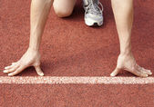 atlet na startovní linii na stadionu
